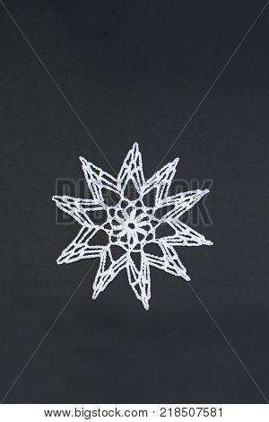 Crocheted star or christmas star, isolated on black