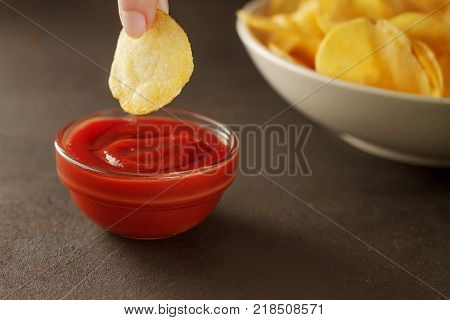 Fingers dips crunchy snack chip into bowl with red sauce. Crispy potato appetizer with tomato dip.