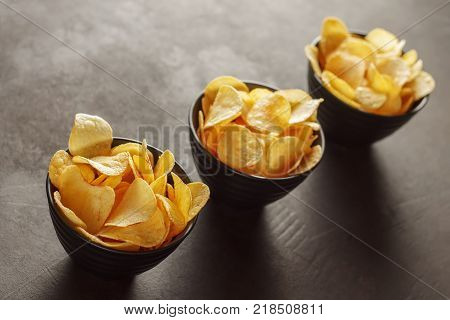 Three black bowls with crunchy potato chips on the table. Concept of unhealty snack food.