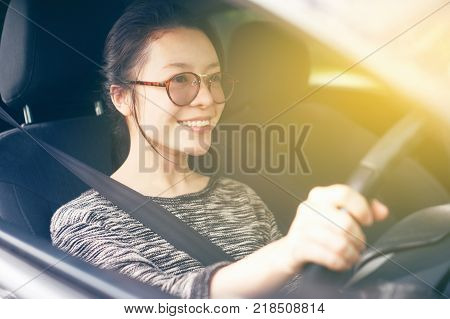 Attractive cute young asian woman in casual wear looking forward while driving a car. smile and happy time to travel or rest concept. filtered image. soft light effect added. fasten seat belt.