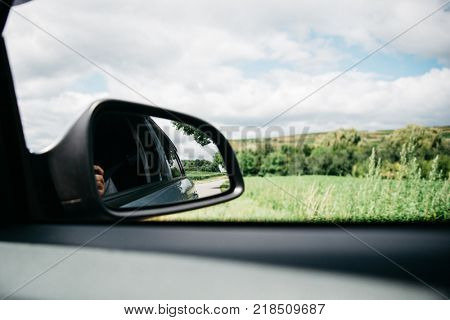 Reflection of asphalt highway road at the car side mirrow. Travelling by car summer season, scenic landscape through car window
