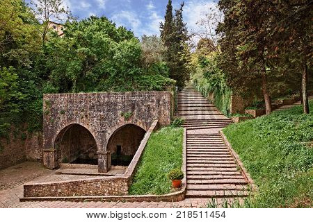 Volterrra, Pisa, Tuscany, Italy: the ancient Fonte di Docciola, a fount built in 1254 at the entrance of the old town and the staircase that leads to the historic city center