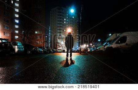 a mysterious man stands alone in the street among cars in an empty city weat road after the rain walks the night street dreams