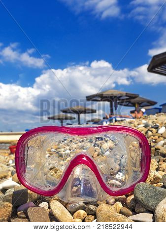 Mask for scuba diving on a pebble beach. Underwater masks and tubes in the water on pebbles on the sea coast. The concept of a dive or the concept of a summer sea voyage. Equipment for diving.