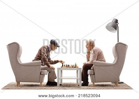 Elderly man and an elderly woman seated in armchairs playing a game of chess isolated on white background