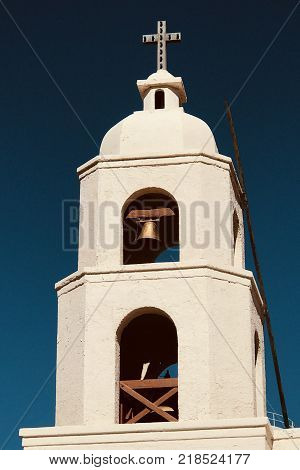 Old world church steeple with cross and bells