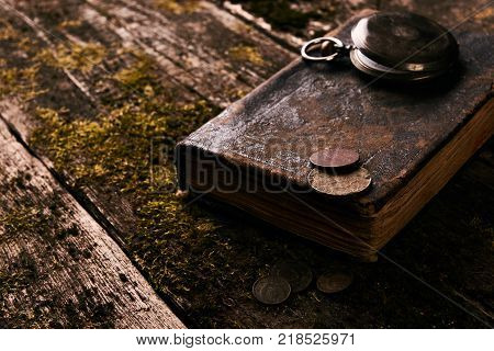 Vintage pocket watch with old antique bible book and retro coins money on a grunge wooden background. Antiques in an antique shop
