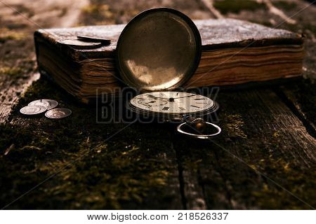 Retro vintage pocket watch with an old antique bible book and ancient copper coins on a grunge wooden background. Antiques in an antique shop