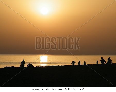 Shore of the Black sea on a hot evening, the Black sea coast of the Caucasus. People walk on the shore; 2010