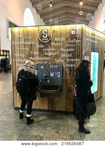 Stuttgart, Germany - December 09, 2017: People are using a vending machine offering fair produced local food and drinks in the main station of Stuttgart in Germany.