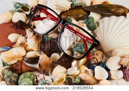 Summer beach accessories sunglasses with colorful mix sea shels, starfish, shellfish, seashell, scallops. Travel concept close-up