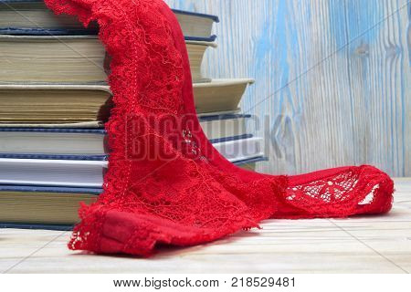 Red lace g- string and a pile of old books on the table in the university library. Red lingerie