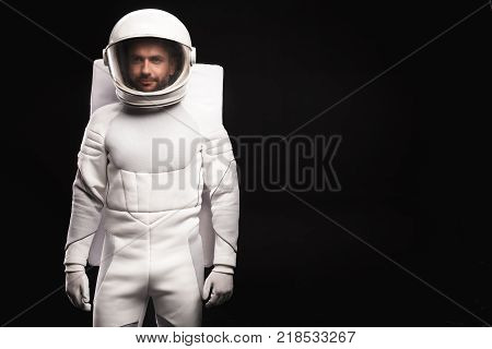 Ready for new discovery. Portrait of concentrated young cosmonaut wearing hyperbaric astronaut protective suit is standing and looking at camera confidently. Isolated background with copy space poster