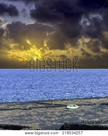 Dramatic sunrise over the ocean before storm with empty boat - Los Cocoteros, Lanzarote, Canary Islands, Spain