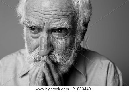 Close up black-and-white portrait of aged distressed pensioner expressing sorrow. Isolated on grey background