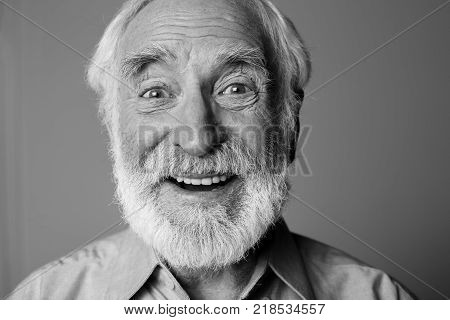 Sincere amazement. Close up black-and-white portrait of aged happy pensioner with widely open eyes while standing. Isolated on grey background
