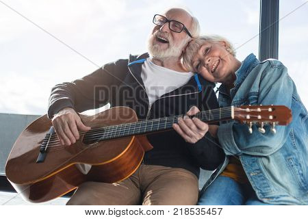 Romantic moments. Waist up portrait of two mature pensioners sitting on windowsill. Man is performing composition on guitar