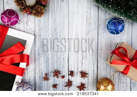 Holiday New Year concept, gifts wraped with red ribbon and bright flippery on wooden background with space for text