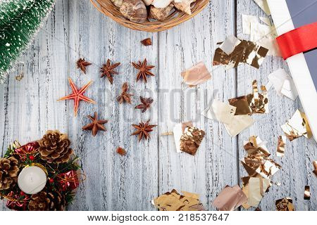 Christmas objects cones, christmas tree, candle, star, gift wraped with a red ribbon and tinsel on light grey wooden background
