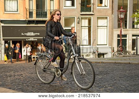 AMSTERDAM/ NETHERLANDS - OCTOBER 25, 2014. Fashionably dressed young woman in a short skirt riding a bicycle. Bridge Torensluis, Amsterdam, the Netherlands.