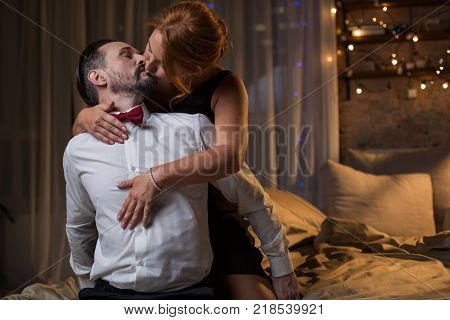 Passionate loving couple is kissing in bedroom. Woman is embracing man from behind with desire. Prelude concept. Copy space