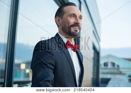 Side view of excited man in suit enjoying city view on balcony and laughing