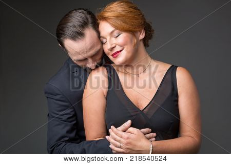 Waist up portrait of glad middle-aged woman enjoying hug of her husband. Man is standing and kissing female shoulder with passion. Isolated