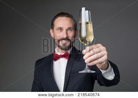 Cheers. Joyful man in suit is proposing toast while stretching glass forward. He is standing and smiling. Focus on champagne. Isolated