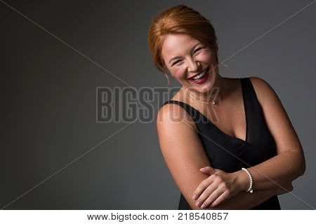 Waist up portrait of happy middle-aged woman standing in elegant black dress. She is looking at camera and laughing. Isolated and copy space