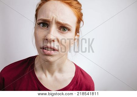Unhappy handsome girl with ginger hair and freckles, looking in camera with angry and unsatisfied expression