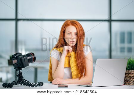 sad redhead girl video blogger sitting at table with laptop and looking at camera