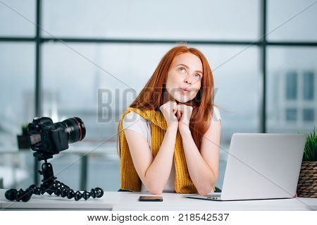 happy redhead female blogger with laptop think about new theme for vlog.