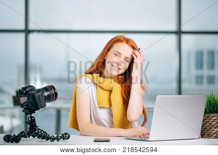 Young female blogger with laptop and book on camera screen looking at camera.