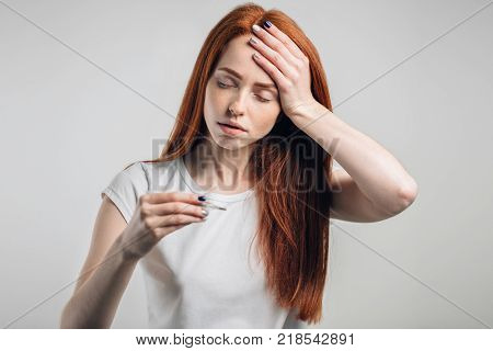 Young sick woman looking at thermometer. Sick girl with a thermometer on a white background