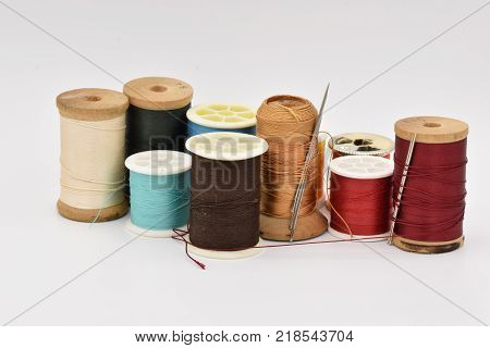 Spools of colored thread arranged on a seamless white background. Thread including blue, red, and black.