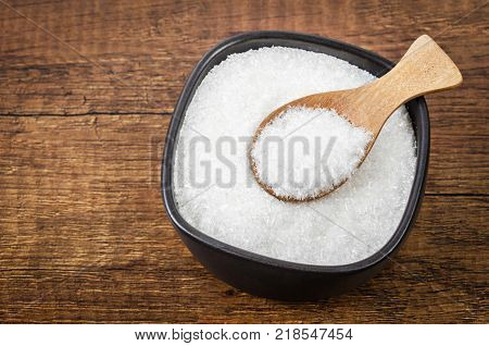 Monosodium Glutamate in black bowl with wooden spoon on wooden background.