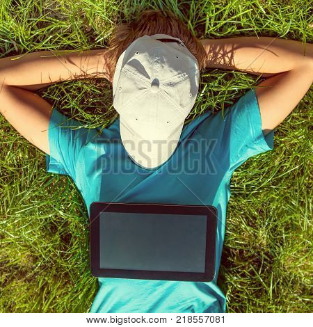 Toned Photo of Teenager with Tablet Computer take a rest on the Grass