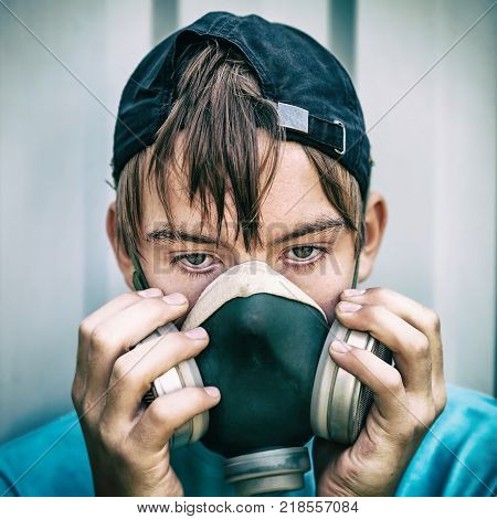Toned Photo of Teenager in the Gas Mask on the Wall Background
