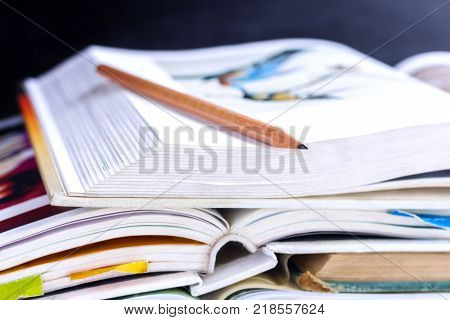 Open hardback and textbook stacked on the table on blackboard background. The concept of intelligence comes from education. focused on the textbook. poster