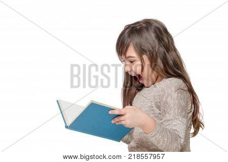 Side view of laughing surprised long haired little girl holding an open book . All is on the white background.