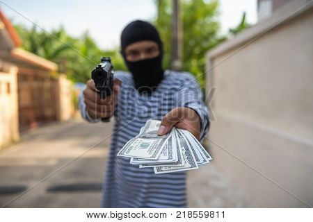 Robber aiming a gun to taking money from victim tourist on the walking street. Criminality concept