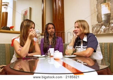 Two Mulatto Girls Are Listening To Blond Guy While Drinking Coffee In A Cafe