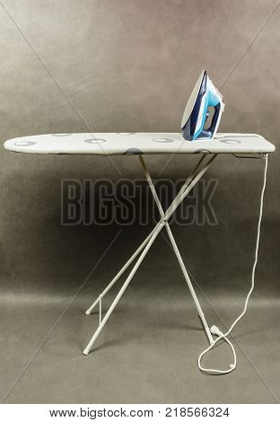 Ironing board with a clothes iron on a gray background.