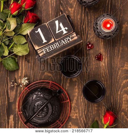 Valentine's day flat lay with green tea, black teapot, candles, roses and wooden calendar. Valentines day concept. Top view.