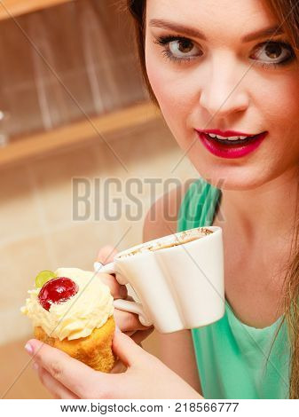 Woman drinking coffee and eating delicious gourmet sweet cream cake. Glutton girl sitting in kitchen with hot beverage and cupcake. Appetite and gluttony concept.