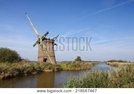 Derelict windmill stands beside a drainage ditch in the Norfolk Broads