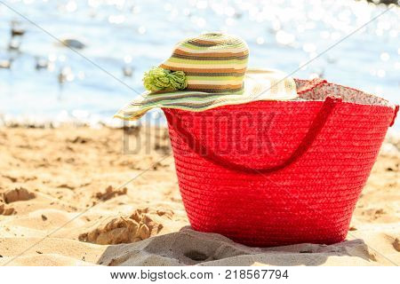 Wicker basket handbag bag purse and hat on beach sand. Summer holiday vacation.