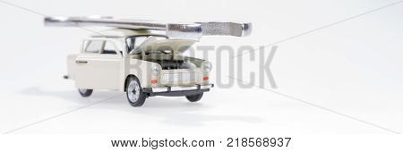 Car service - bright toy car and big wrench isolated on white