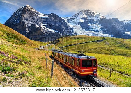 Famous electric red tourist train coming down from the Jungfraujoch station (top of Europe) in Kleine Scheidegg, Bernese Oberland, Switzerland, Europe