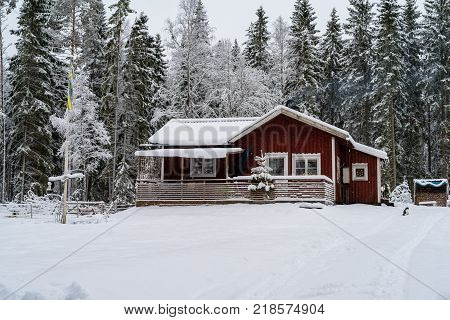 A little red cabin in a forest covered in snow standing in Sweden